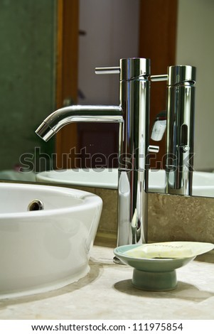 Silver chrome bathroom tap faucets running water in a sink - stock photo