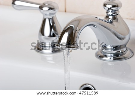 Silver chrome bathroom tap faucets running water in a sink