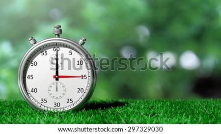 Silver chronometer on green grass - stock photo