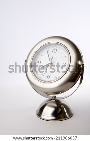 Silver clock. A brushed chrome clock on a stand showing the time approaching 4 o'clock. Studio lighting isolated on a white background.