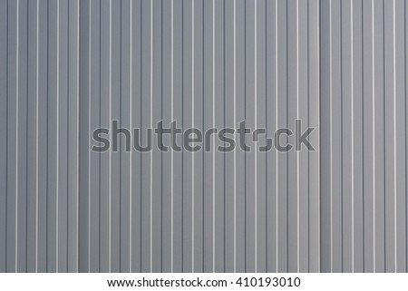 Silver-colored metal wall corrugated sheet metal background. - stock photo