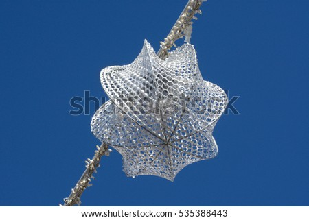 Silver colored outdoor Christmas ornament and lights against blue sky