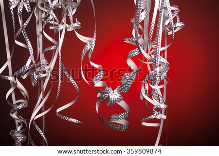 Silver colored streamers in front of a red background with vignette