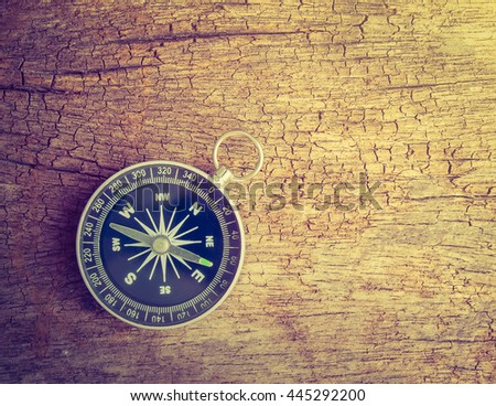 silver compass on wood with vintage color