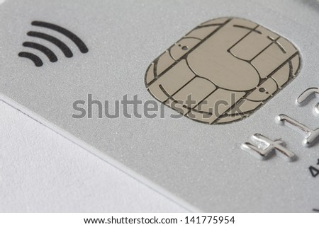 Silver credit card showing electronic chip - stock photo