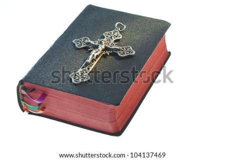 silver cross on old holy bible, isolated on white background