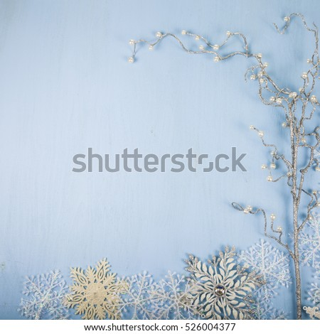 Silver decorative snowflakes and branch on a blue wooden background. Christmas decorations closeup.