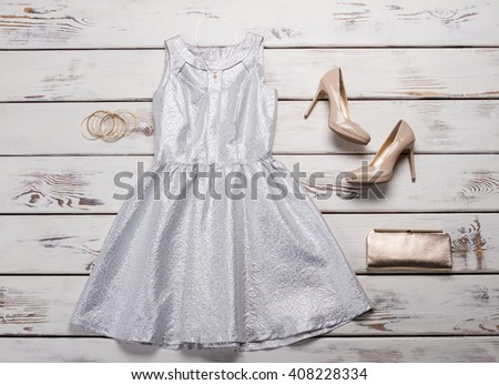 Silver dress with beige shoes. Silver dress on wooden table. Luxury evening outfit for ladies. Special offer at clothing shop. - stock photo