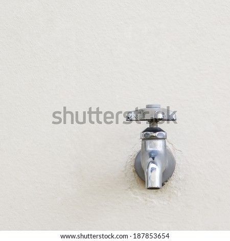 Silver faucet on white wall - stock photo