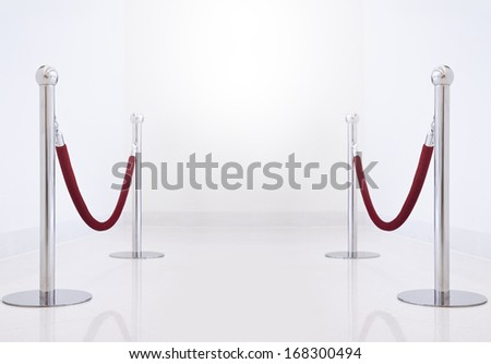 silver fence, stanchion with red barrier rope. - stock photo
