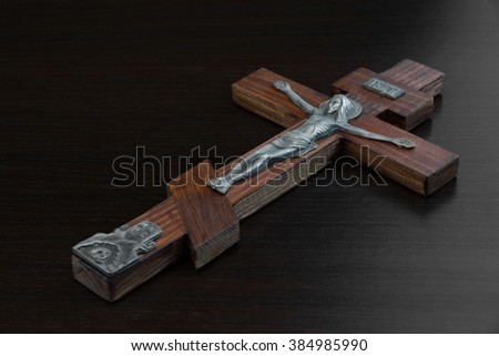 Silver Figurine of Jesus Christ Crucified On Red Wood Cross In Spotlight On Black Background, Religion Concept, Closeup, Top View - stock photo