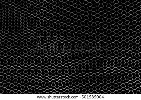Silver, filigree wire mesh in front of a black wall