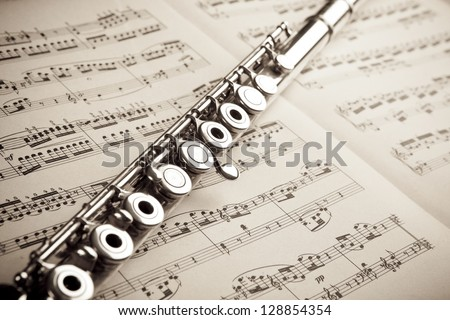 Silver flute on an ancient music score background