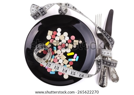 Silver fork and knife on colored pills in  black plate isolated on white background - stock photo
