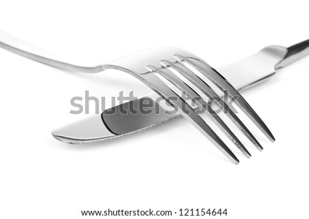 Silver fork over silver knife on a white background