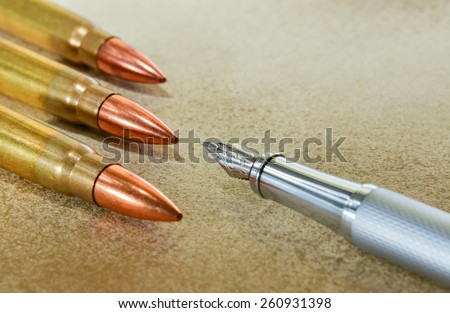 Silver fountain pen and three bullets arranged in the corners of the image - stock photo
