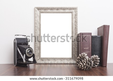 Silver Frame with old books and old camera on wood table - stock photo