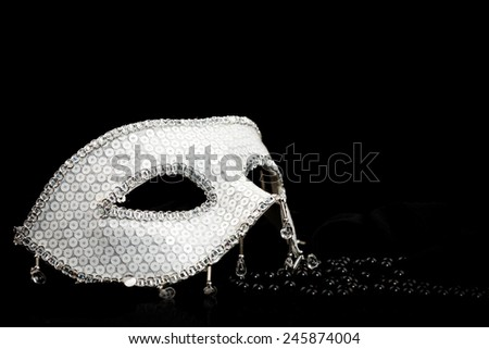 Silver glittering carnival mask and black pearls  - stock photo