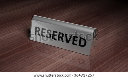 Silver glossy reservation sign on wooden surface with reflection
