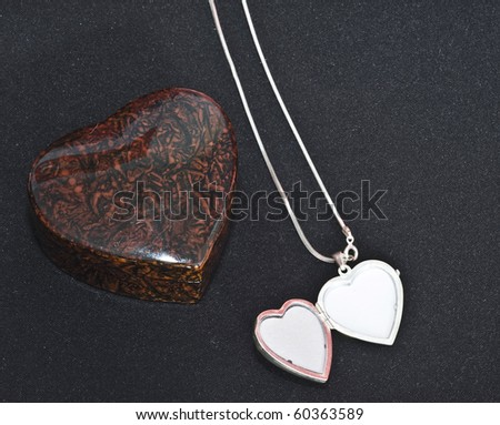 Silver heart and heart shaped box for jewelery with some silver necklaces and rings - stock photo