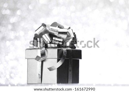 Silver holiday gift on glitter background - stock photo