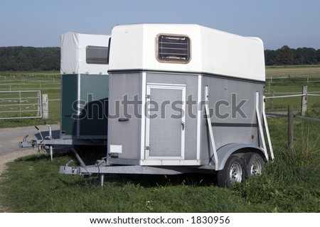 silver horse trailer on green weadow