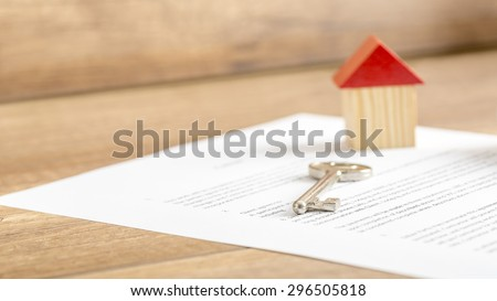 Silver house key lying on a contract of house sale, lease, insurance or mortgage in a real estate concept, viewed low angle with focus to the tip. - stock photo
