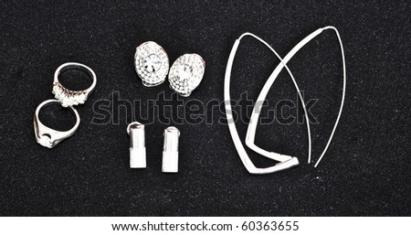 Silver jewelery - earrings, necklaces, rings on black background - stock photo