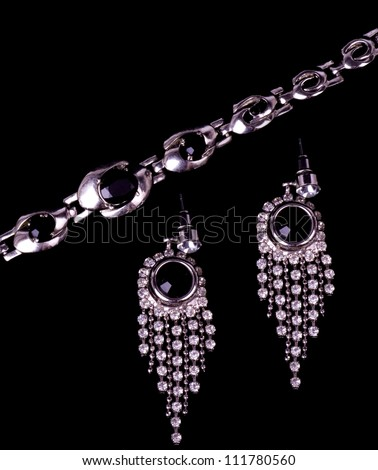 Silver jewelry on black background - stock photo