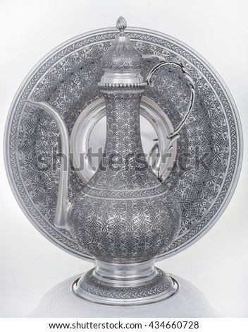 silver jug with plate on a white background, Close up photo of handmade silverware that is delicately handcrafted, Custom made authentic designs are the key factor in getting the fine art made. - stock photo