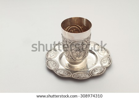 Silver kiddush wine cup and saucer on a white background