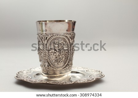 Silver kiddush wine cup and saucer on a white background - stock photo