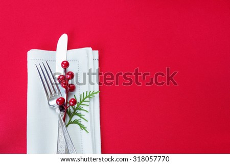 Silver knife and fork, and red holly berries and green thuja branch lie on the white linen napkin, which is located on a table covered with a red tablecloth, top view - stock photo