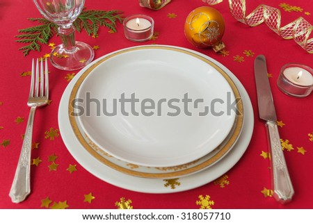 Silver knife, fork, dinner plates, wineglass and burning candles, which is located on a table covered with a red tablecloth - stock photo