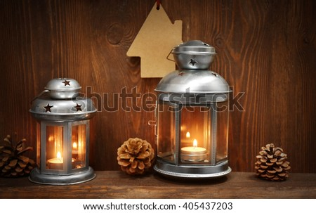 Silver lanterns with pine cones on wooden background