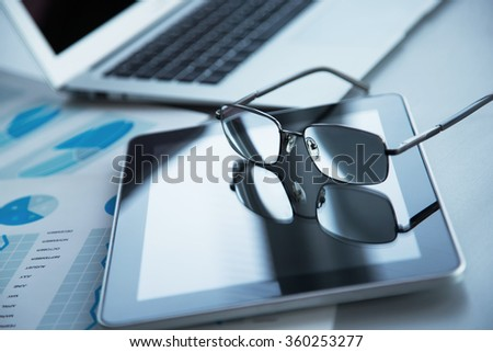 Silver laptop, tablet and  glasses on table
