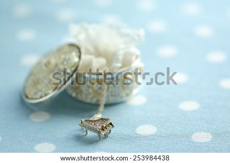 silver locket / piano - stock photo