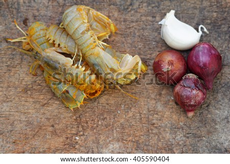 Silver mantis shrimp or known as udang ketak and udang lipan in Malaysia with small onion and garlic on old wooden chopping board. Shrimp ready to be cooked after mixed with turmeric and salt. - stock photo