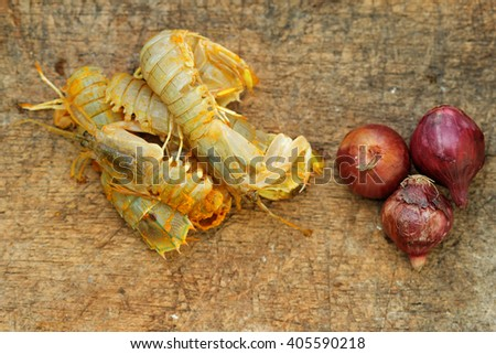 Silver mantis shrimp or known as udang ketak and udang lipan in Malaysia with small onion on old wooden chopping board. Shrimp ready to be cooked after mixed with turmeric and salt. - stock photo