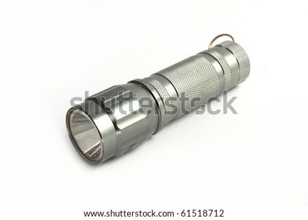 silver metal flashlight isolated on white background. - stock photo
