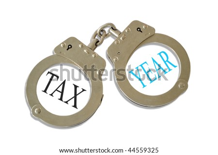 Silver metal handcuffs tax year concept - stock photo