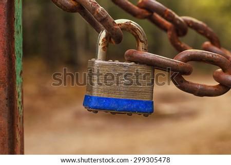 Silver metal lock on a rusty chain. - stock photo