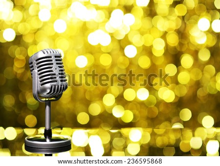 Silver microphone on golden background - stock photo