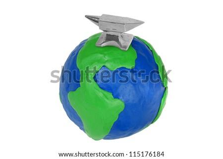 Silver miniature anvil, standing on a plasticine globe - stock photo