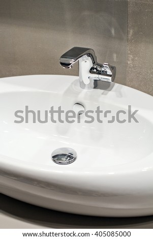 Silver modern faucet sink in the bathroom - stock photo