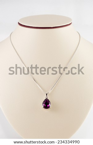 Silver necklace and pendant on white mannequin - stock photo