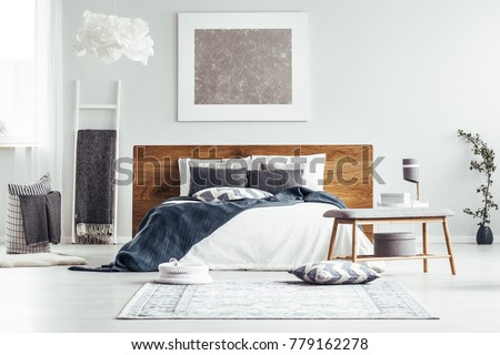 Silver painting on white wall above bed in designer bedroom interior with ladder, lamps and bedsheets