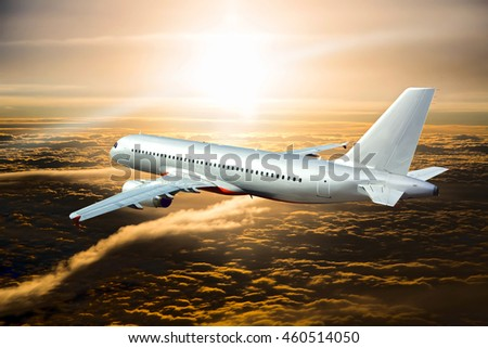 Silver passenger airplane. Aircraft flies over clouds during the sunset time.