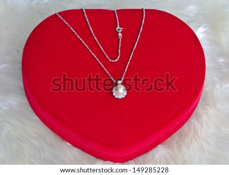 Silver pearl earrings and red velvet box. - stock photo