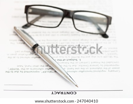 silver pen and eyeglasses on pages of sales contract - stock photo